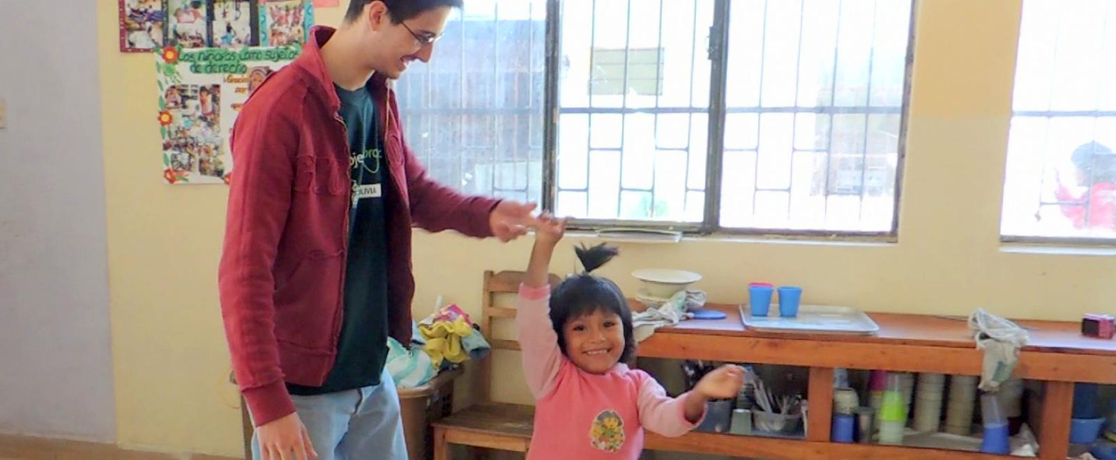 Projects Abroad Early Childhood Development volunteer dancing with a child during his spring break project placement